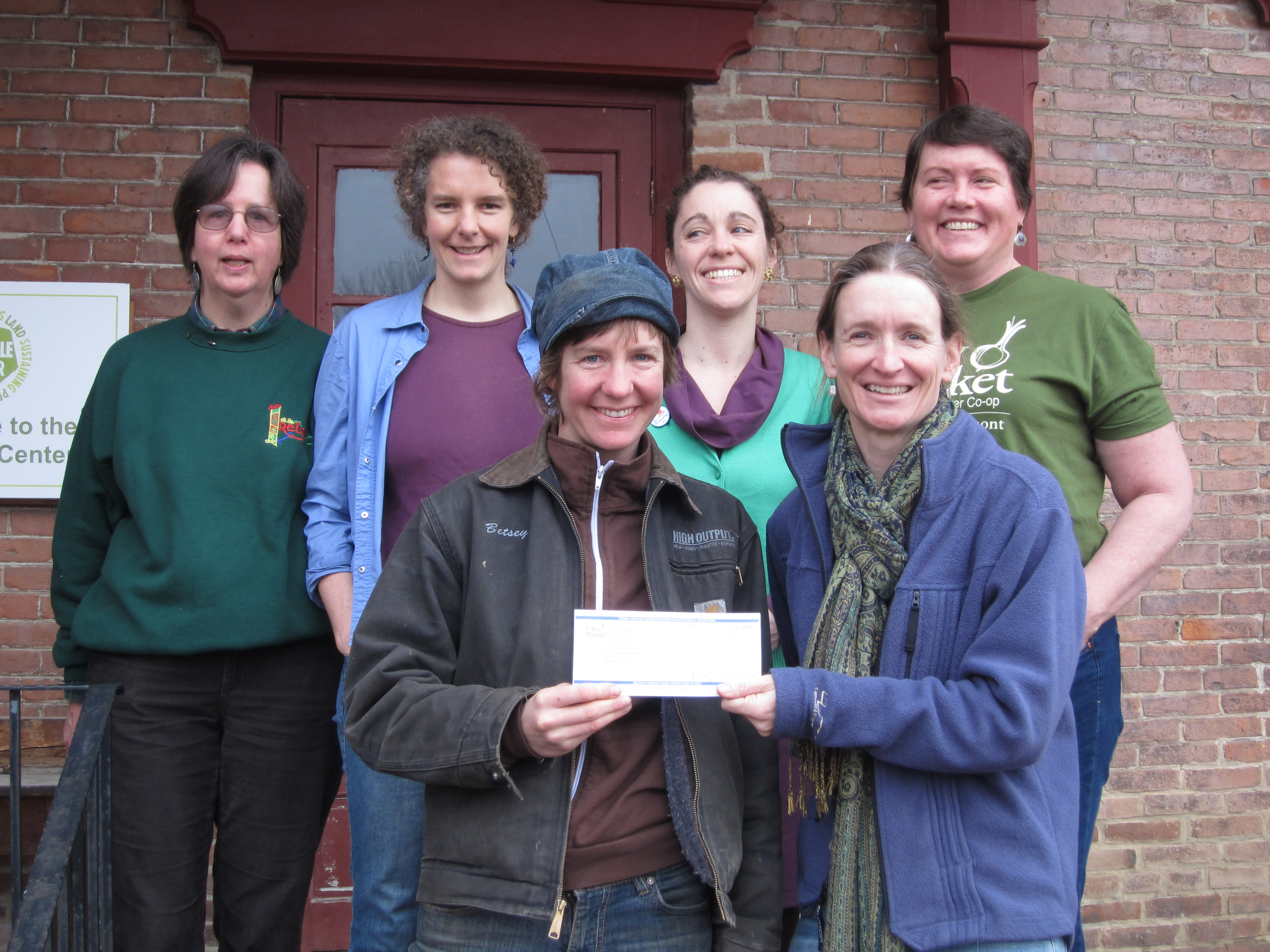 Susan Munkres, Board President of City Market (front row, right) presents a donation check to Hilary Martin, President of The Intervale Farmers' Equipment Company. Pictured here with other City Market Board Members (back row, l to r) Nancy Nesbitt, Rachel Jolly, Molly O'Brien, and Maura Finn.