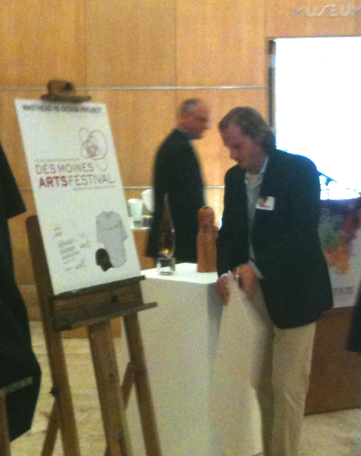 Spindustry's Howard Tempero revealing the new Des Moines Arts Festival r logo design at the Des Moines Art Center.