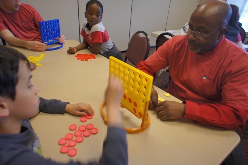 Alliance Data volunteers spent time with kids at the Club, teaching them to play games such as Connect 4. Here, Tony teaches a new friend some winning strategies.