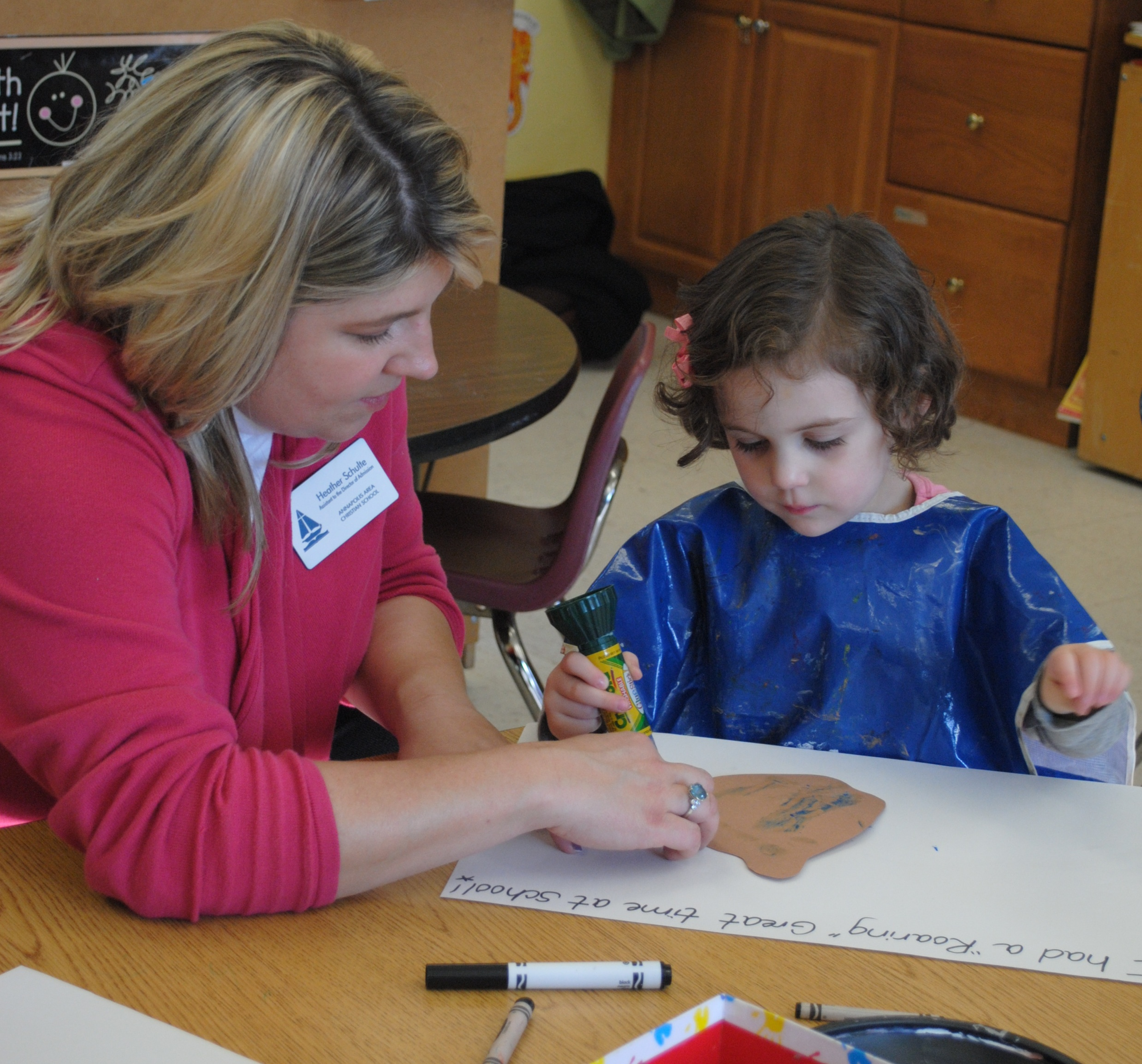 Experiencing a mock school day, Heather Schulte, Assistant to the Director of Admission, works with one of the participants