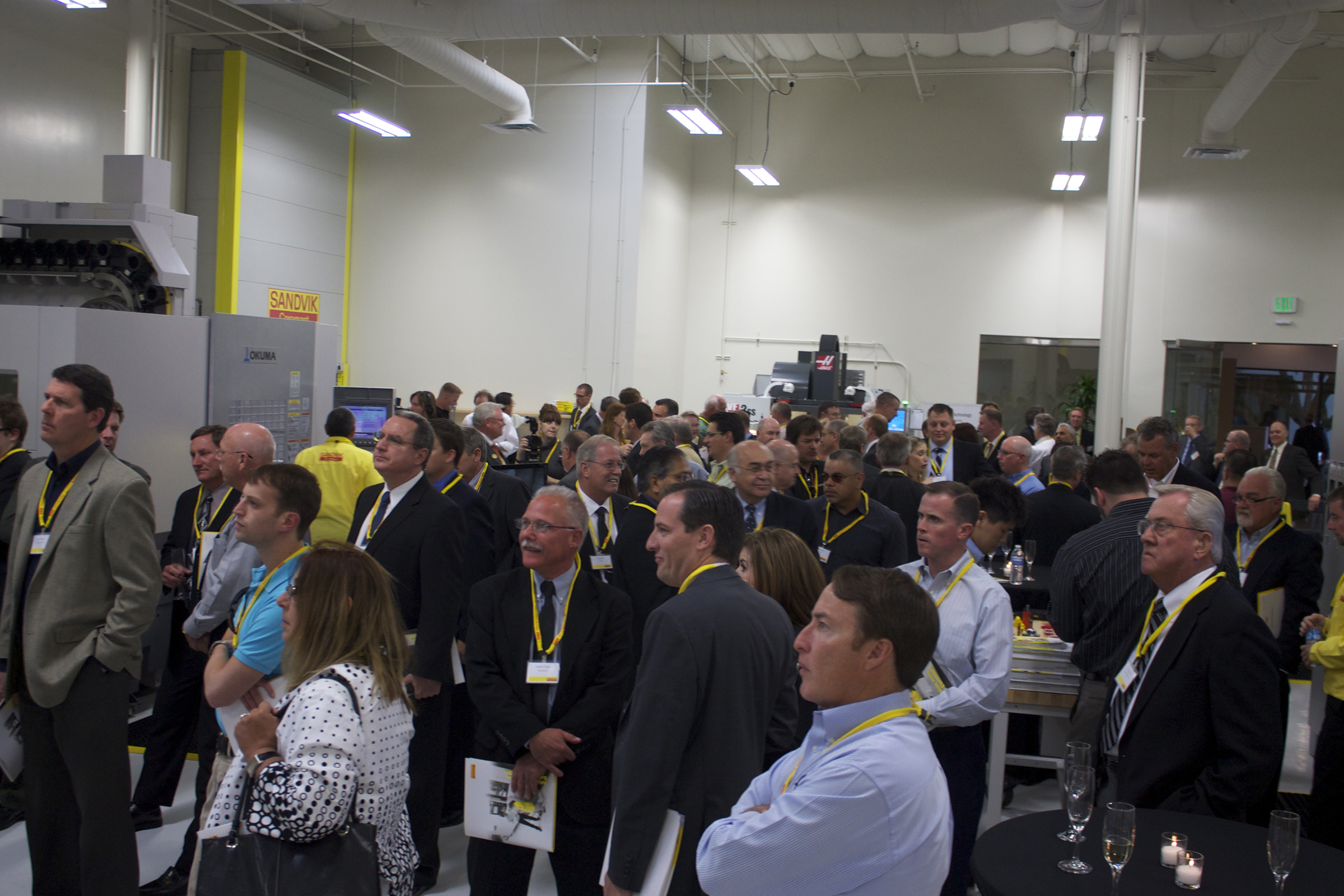 Pictured - Attendees watching a live machine demonstration during the grand opening of the Cypress, California facility.