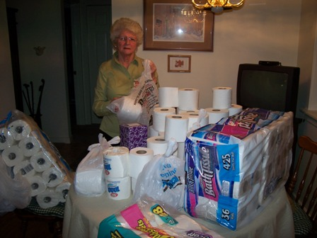 Barbara Sullivan gets the donated toilet paper ready to hand out.