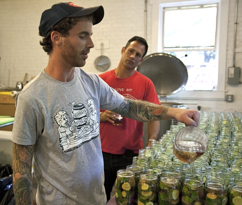 Brooklyn Brine founder Shamus Jones (left) adds 60 Minute IPA brine to pickle jars with Dogfish Head founder Sam Calagione.
