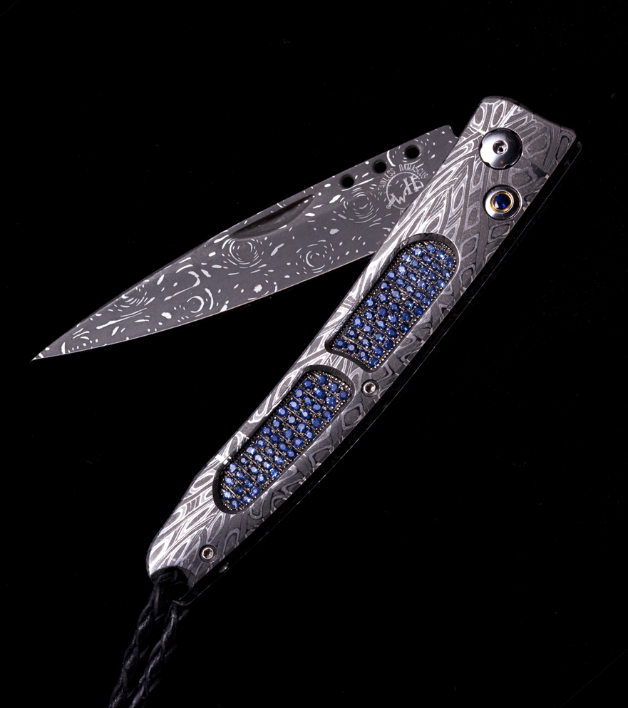 The B06 'Ventana' pocketknife in hand forged damascus, inlaid with a pave of 178 light and dark blue sapphires (2.36K)