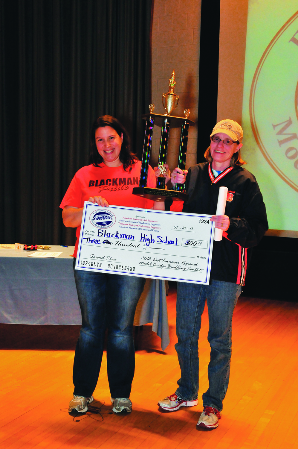 Blackman High School teachers Gail Dawson and Nicole Harvey raise the High Point trophy awarded for the most bridges entered with the highest structural efficiency ratio from one school during the East Tennessee Model Bridge Buillding Contest. Additionally, Blackman High received $300, as the result of their students' bridge building proficiency.