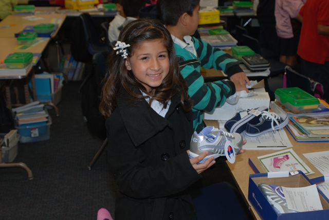 A Lincoln Elementary student in Santa Ana proudly smiles at the sight of her new shoes.