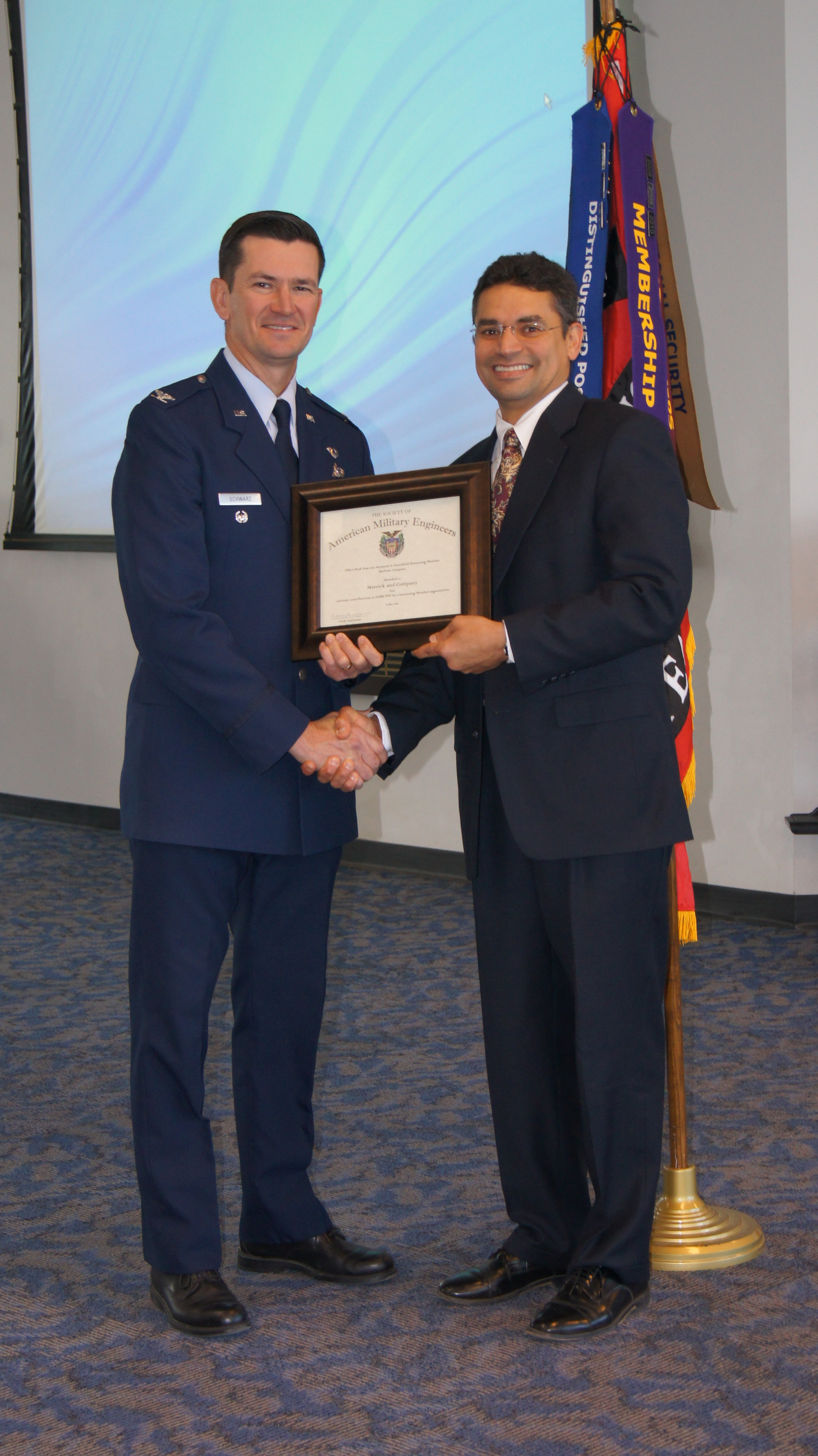 Colonel Joseph Schwarz, HQ Air Force Space Command A7C, Presenting award to Ruben Cruz with Merrick &amp; Company.