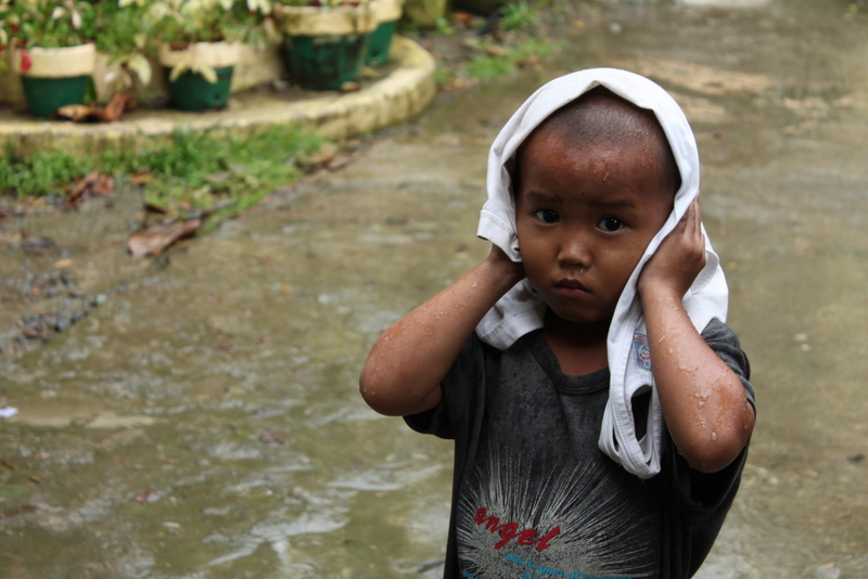 A boy arrives at a distribution of food after floodwaters forced him from his home.