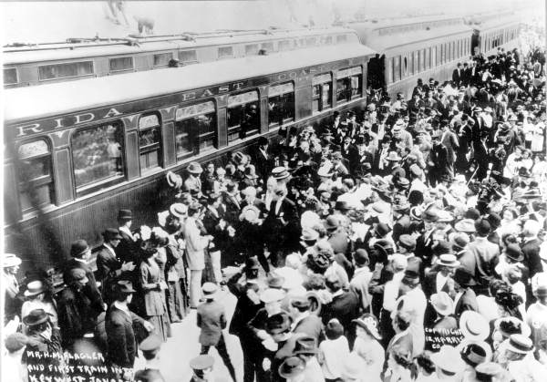 A crowd greets the first train to arrive in Key West, 1912. Henry Flagler is at center in straw hat, escorted by Mayor J. Fogarty holding top hat.