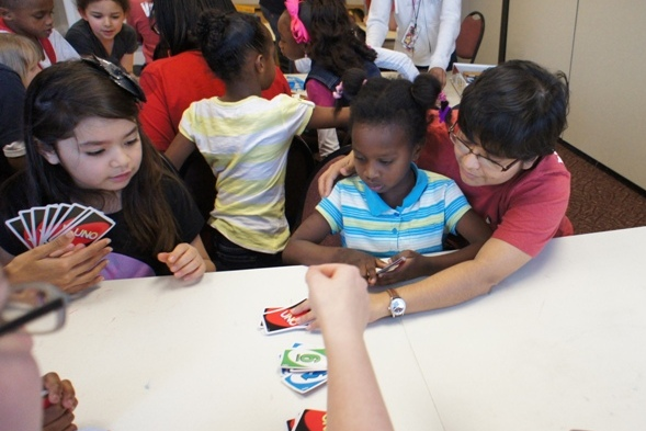 Alliance Data volunteers spent time with kids at the Club, teaching them to play games such as UNO. Here, Laura teaches a new friend how to play the game.