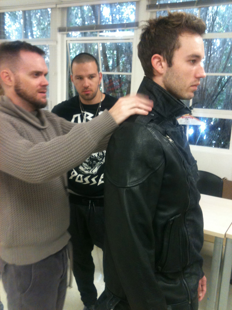 Fashion Designer, Jared Gold, conducting a fitting with promising student, Drew Kessler, in background