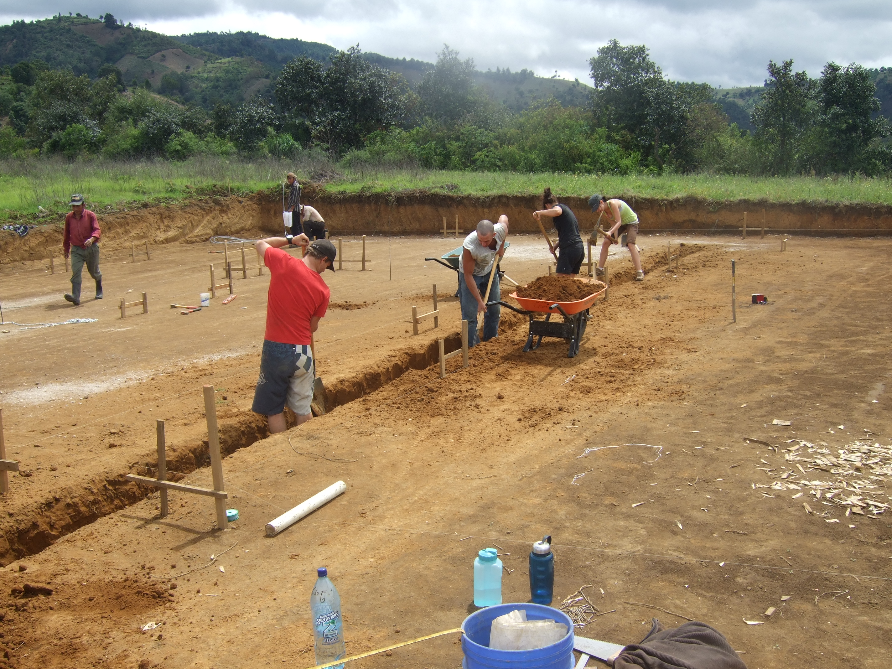 Volunteers digging trenches for the Earthbag home foundations at the Project Somos Children's Village site