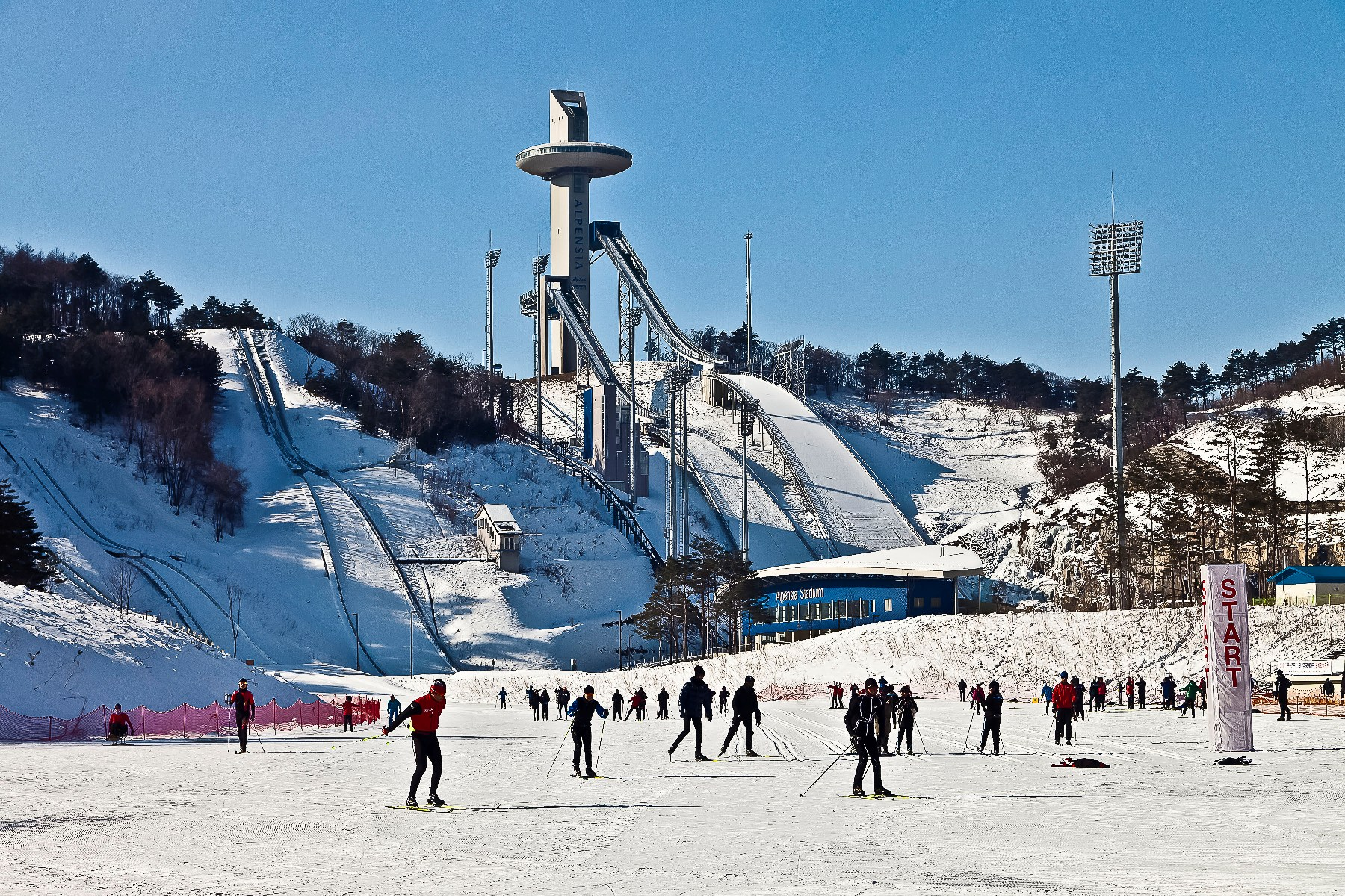 SWA, in collaboration with Space Group architects, created a compact solution that sculpted the K125 and K98 ski jumps with minimal grading, married a Biathlon stadium with a pre-existing Biathlon shooting range, and fit a Cross Country stadium between the two.  Image courtesy Tom Fox SWA Group.