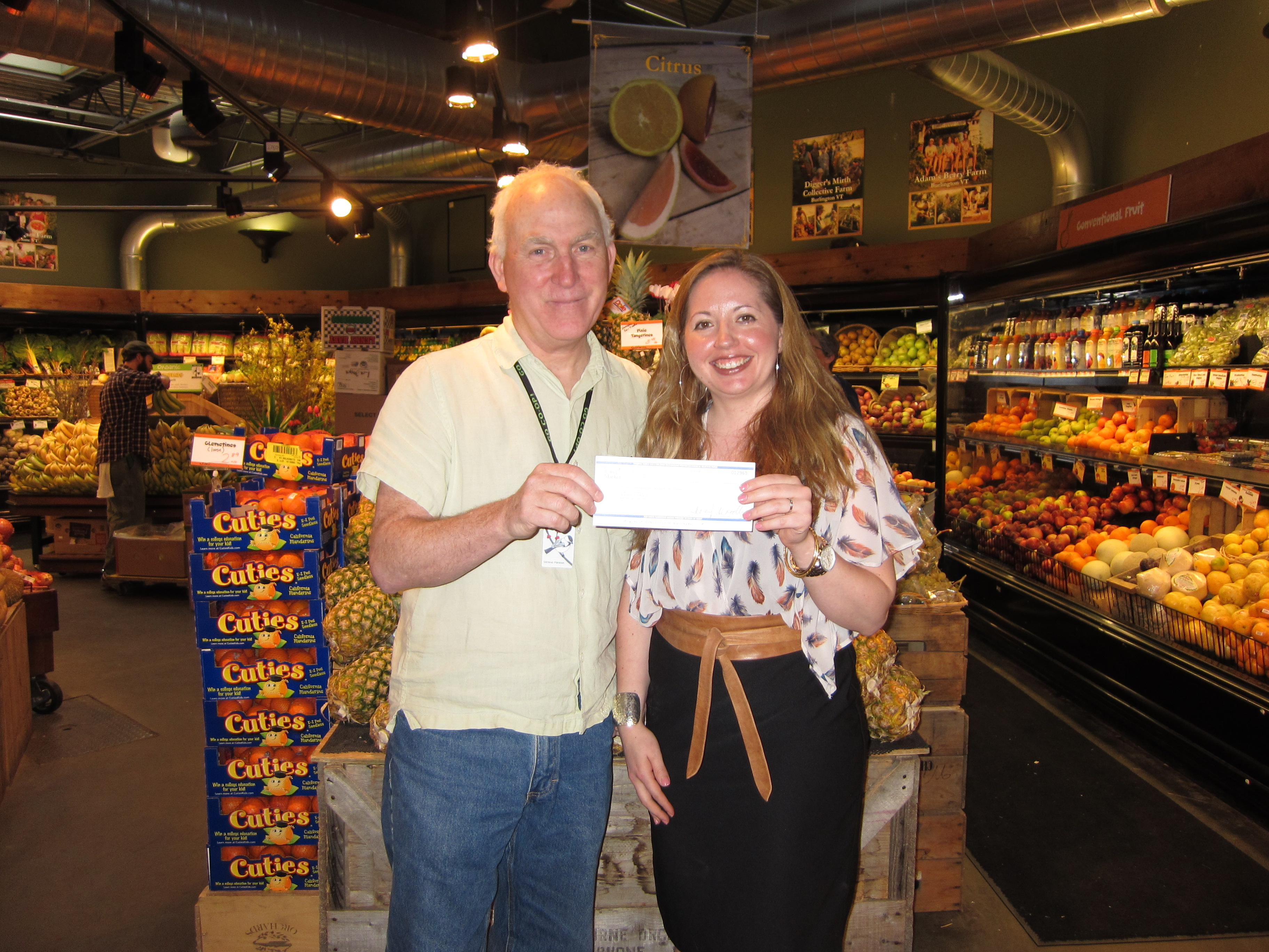 Clem Nilan, General Manager of City Market, presents a donation check to Marissa Parisi, Executive Director of Hunger Free Vermont.