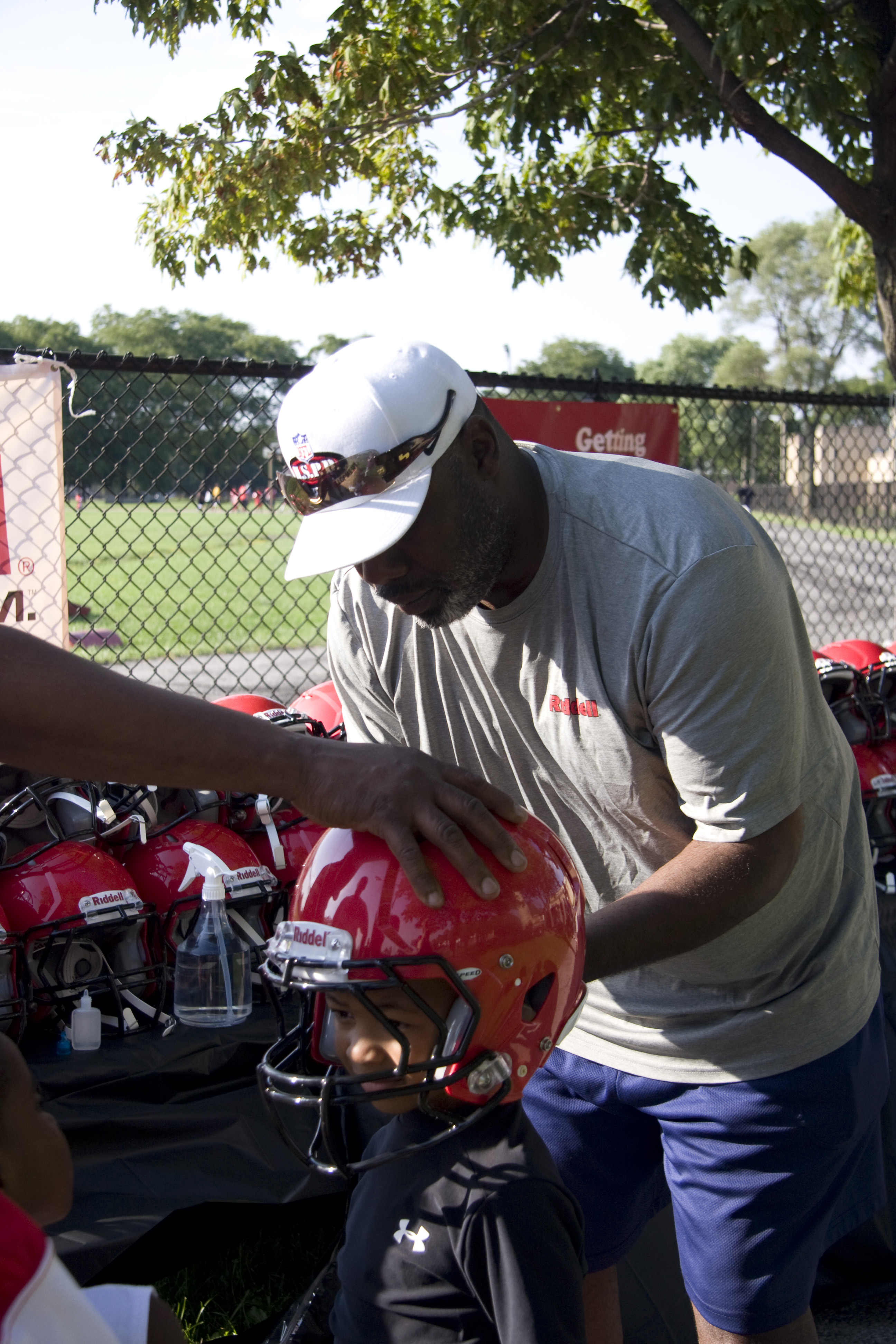 Riddell employee, Milton Biggins, helps CYSO youth football player with a helmet fitting