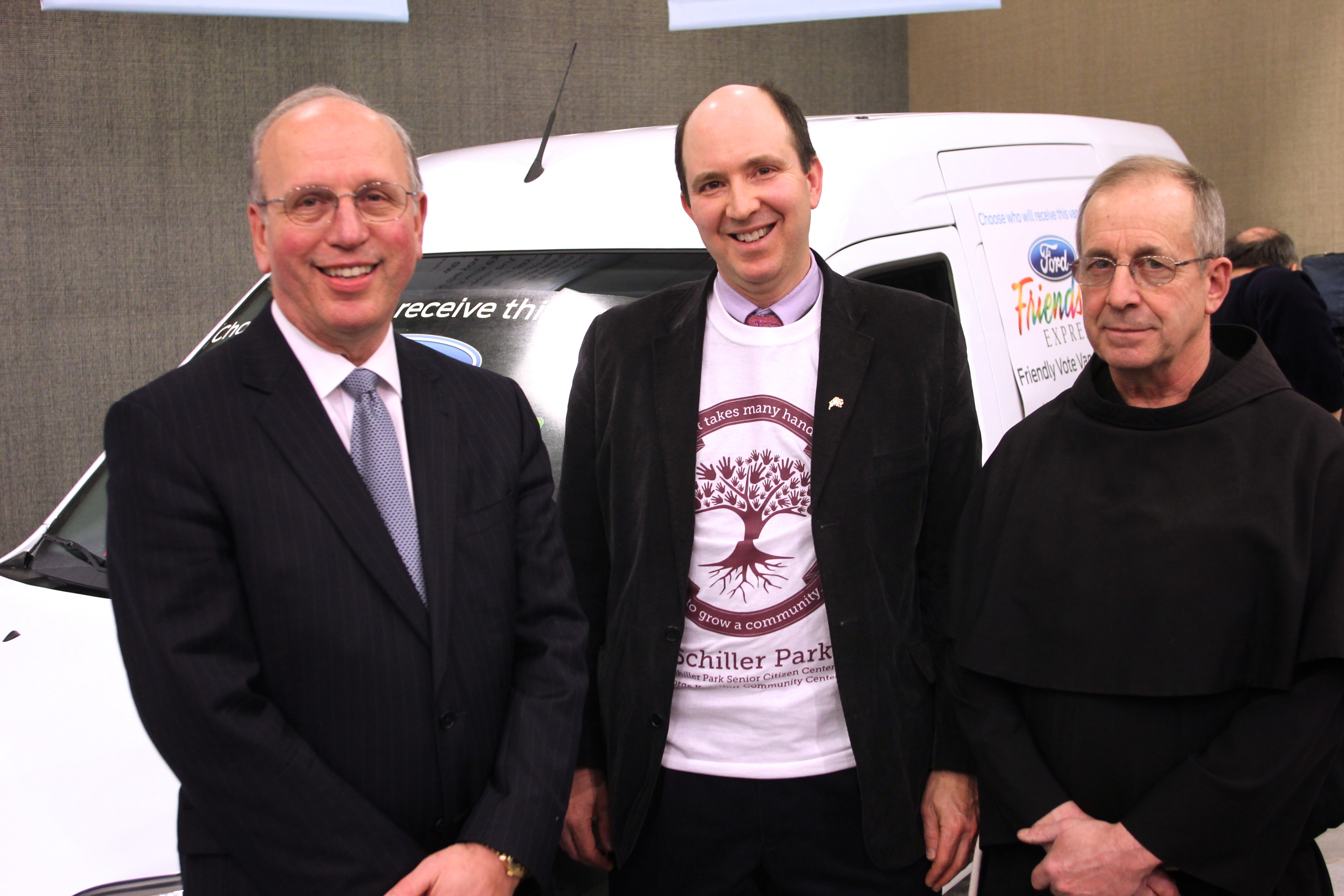 Scott Bieler, chairman of Ford Friendship Express Selection Committee, congratulates Ford Friendship Express van recipients: Michael Tritto, Schiller Park Community Services, Inc.; and Brother Brian, The Franciscan Center.