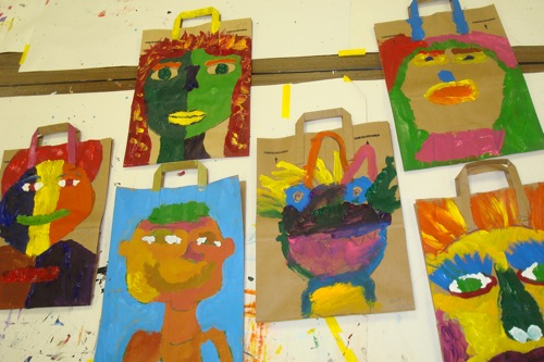 Self Portraits, by Transition Class, St. Francis High School, acrylic paint on paper grocery bags