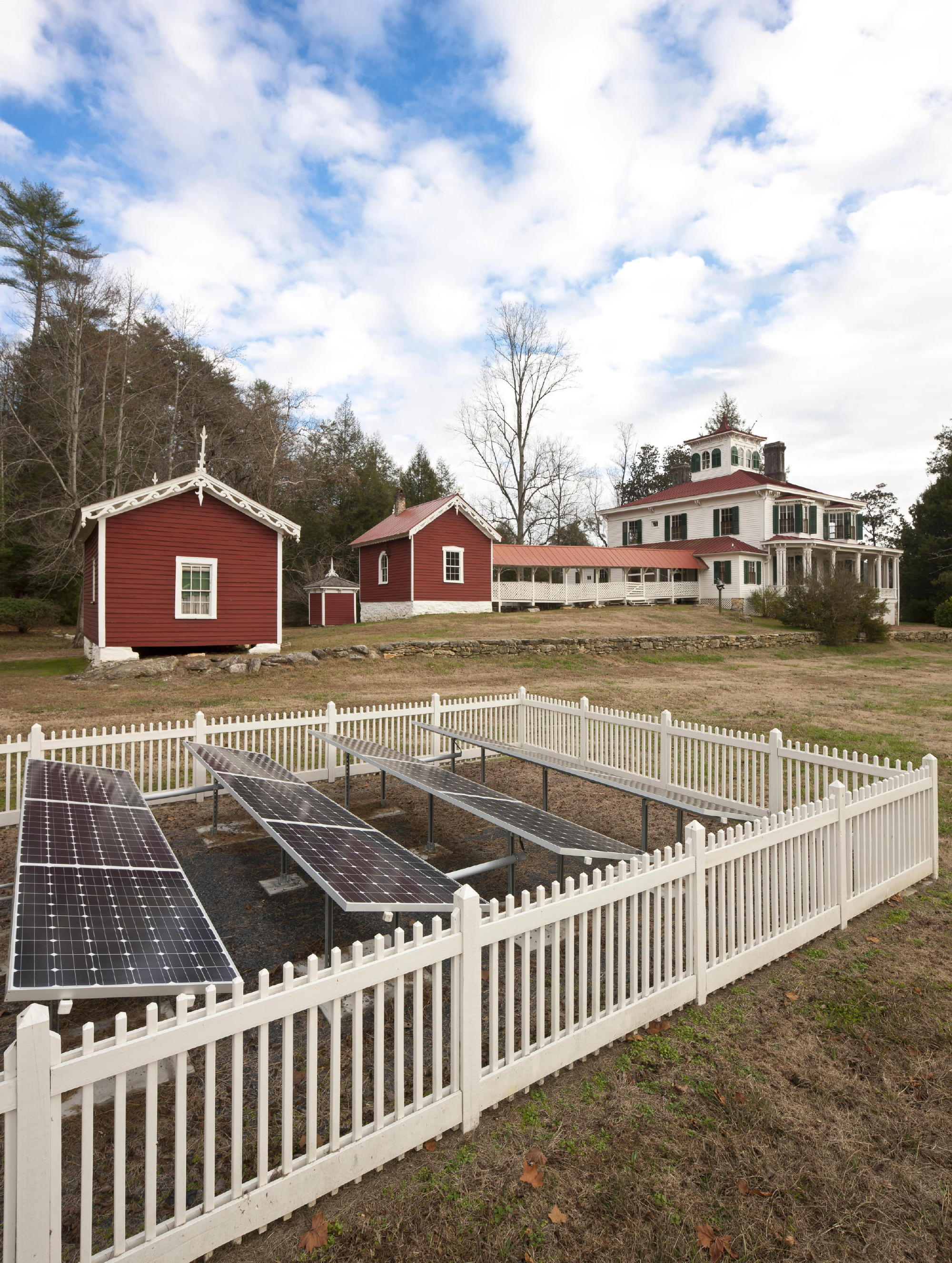 In keeping with the history of early adoption of technologies like indoor plumbing and electricity by the first owners, the design-build team selected an unobtrusive but sunny area near the farmhouse for the installation of 22 solar panels surrounded by a picket fence. Photo: c Jonathan Hillyer / Atlanta