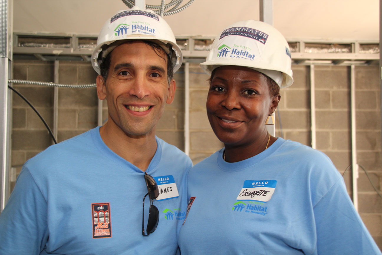 Georgette Lee, future St. John's Habitat homeowner, takes a break from building with James Cava of Citi.