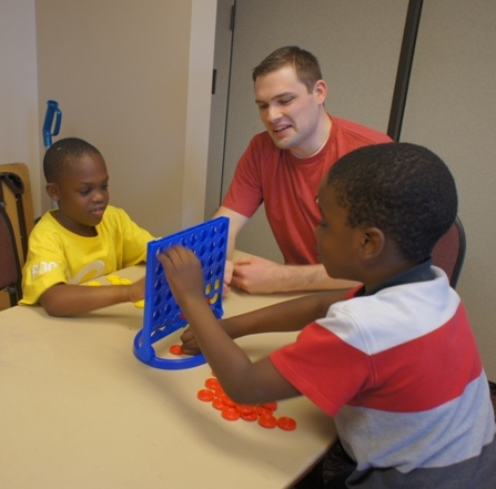 Alliance Data volunteers spent time with kids at the Club, teaching them to play games such as Connect 4. Here, Scott teaches a couple new friends how to play the game.