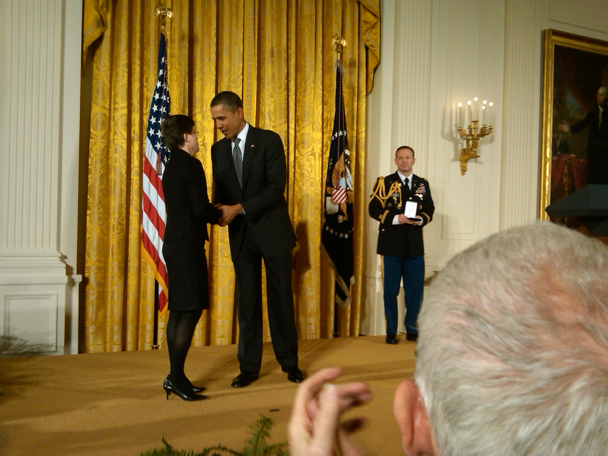 Dr. Cathy Gorn accepting the medal from Barack Obama, the president of the United States. 