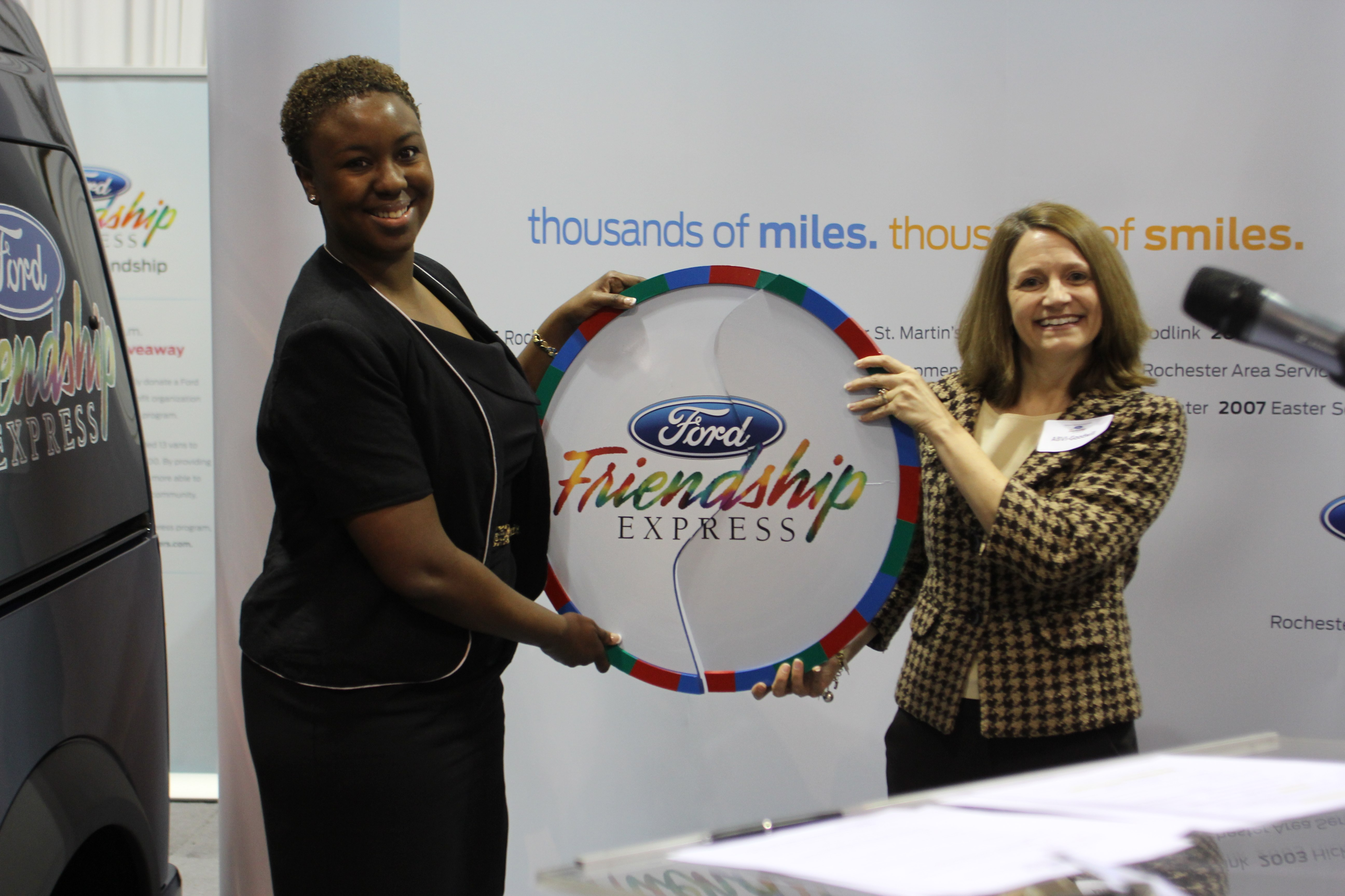 "Ford Friendship Express Selection Committee member, Aki Henderson, completes the ""token of friendship"" with Tracy Schleyer of ABVI-Goodwill, the 2012 Ford Friendship Express van recipient."