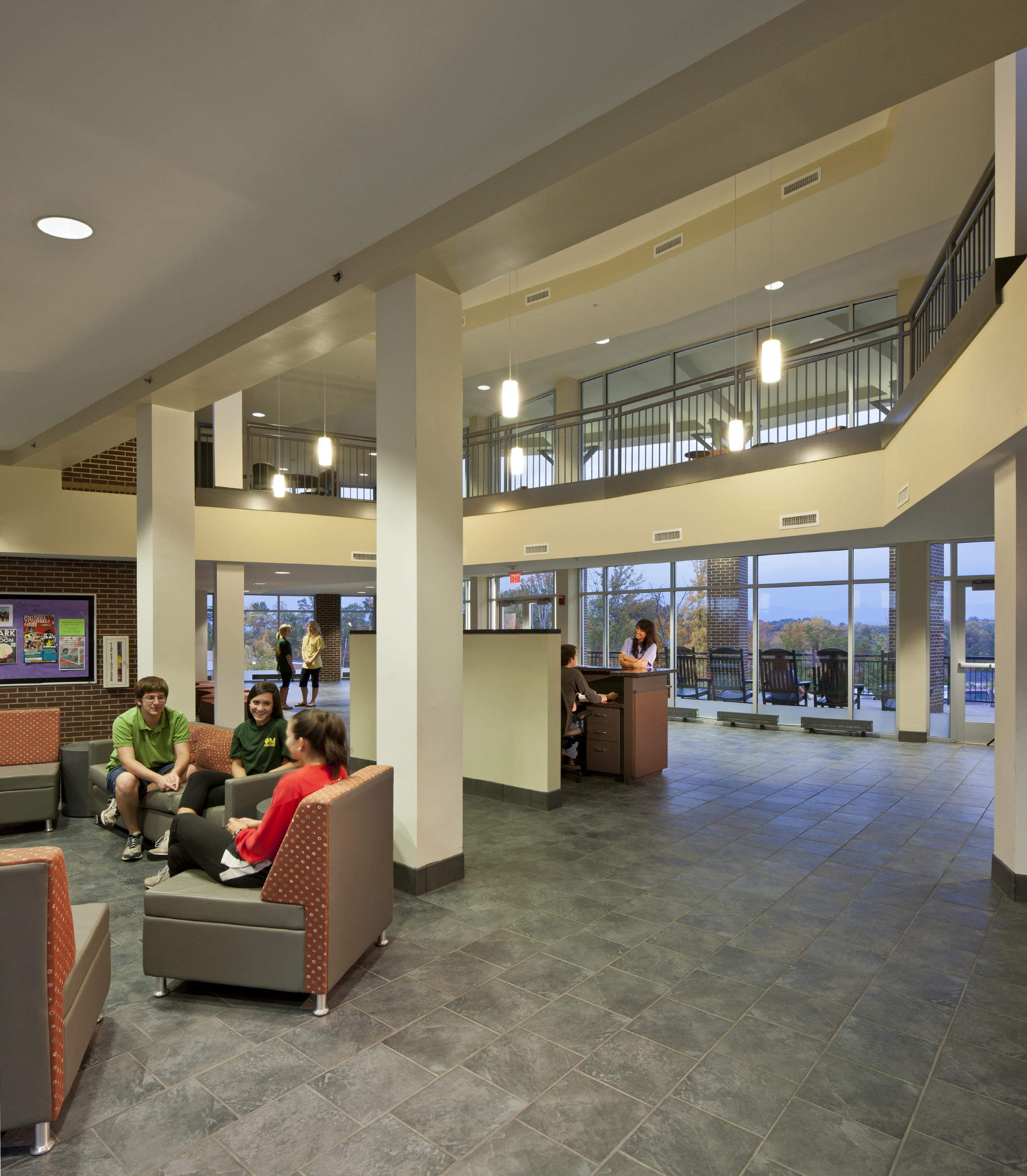 The two-story lobby at North Georgia Suites at North Georgia College & State University serves as a joint community area with shared social areas, kitchens and media, game and pool rooms. The lobby features a granite stone fireplace and great views of the mountains through its front and back floor-to-ceiling glass entries. Photo copyright 2011 Jonathan Hillyer / Atlanta