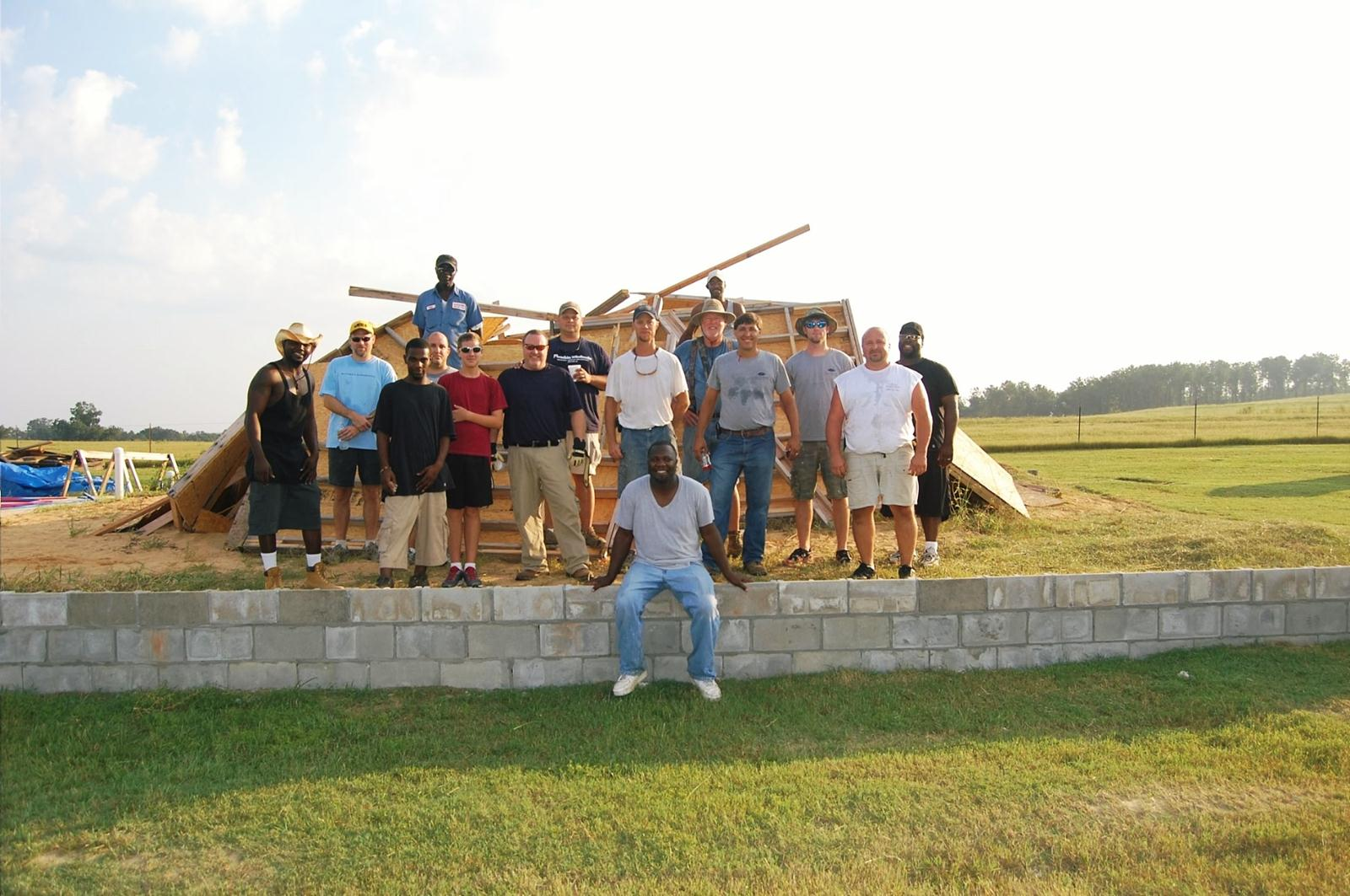 Volunteers pose on the foundation of Clio Community Church.