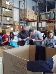 DaVita teammates help sort clothing as a part of a recent Village Service Day.