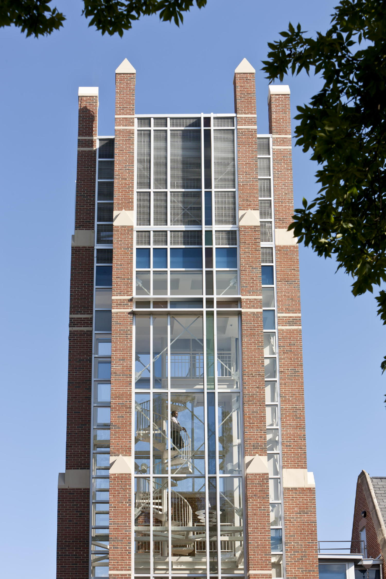An 80-foot-tall glass, steel and masonry bell tower - complete with a carillon at the top - joins the former dormitory with one of the new classroom wings. The tower's brick and cast stone piers are infilled with clear, low-iron glass and a window design that incorporates abstracted crosses on each face of the tower. c 2012 Jonathan Hillyer / Atlanta